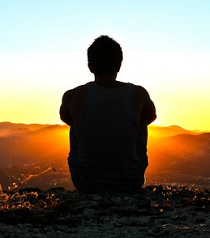 A man meditating at sunset.
