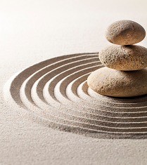 Three stones stacked in concentric circles in sand.