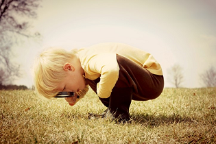 Little boy looking at the ground through a magnifying glass
