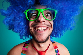 Crazy looking man with blue wig and big, green-rimmed glasses.