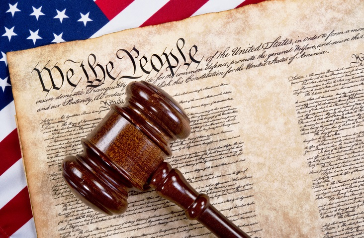 The U.S. Constitution is displayed with a brown gavel on it