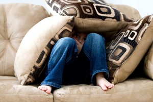 little-boy-hiding-under-cushions_750x500